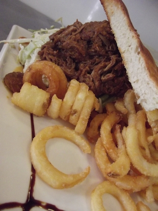 Pulled pork sandwich with apple slaw, bbq sauce and curly fries